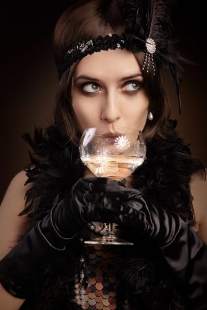 33260249 - portrait of a flapper girl at a party drinking champagne